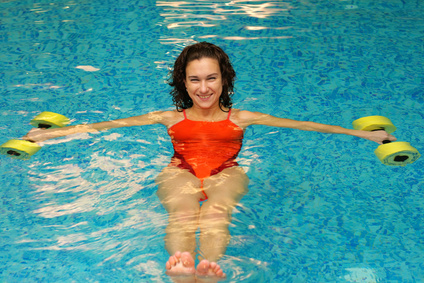 The girl is engaged aqua aerobics with dumbbells