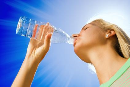 Beautiful blond girl drinking water