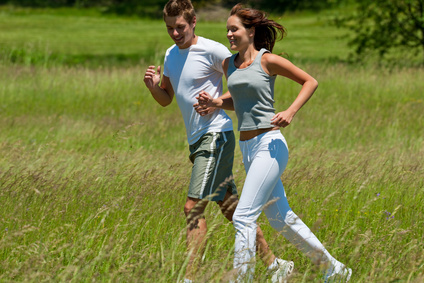 Young man and woman jogging in a meadow