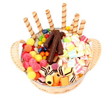 Basket with various sweets and the cookies, isolated